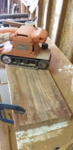 Cleaning up the plank with the belt sander